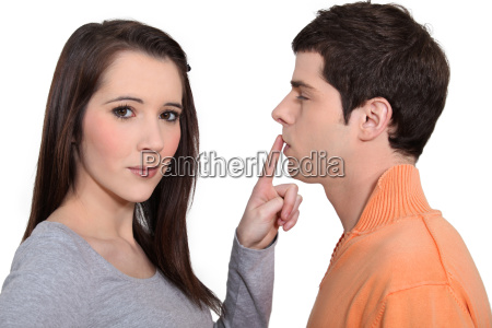 woman with finger touching mans lips
