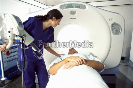 technician guiding patient into mri scanner