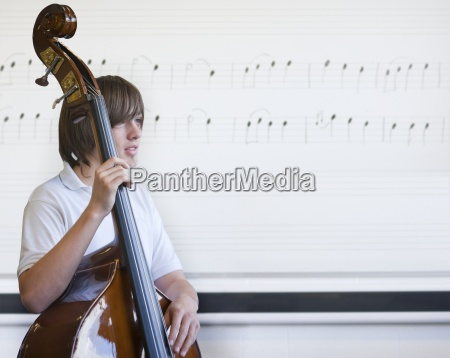 boy holding cello in classroom with