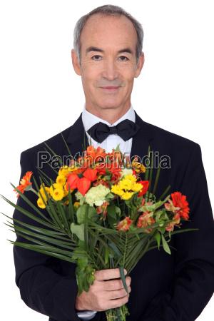 senior gentleman holding bouquet