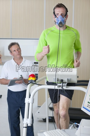 sports scientist monitoring runner with mask