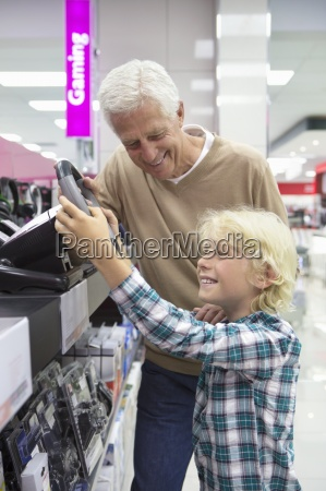 grandfather watching grandson play with video