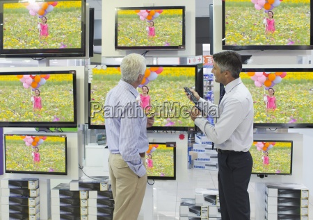 salesman showing senior man flat screen