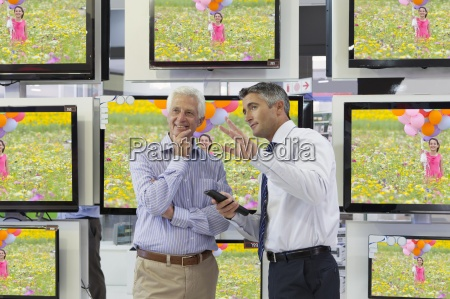flat screen televisions behind salesman and