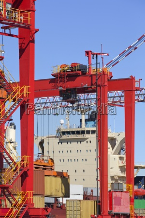 cranes and cargo containers alongside moored