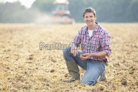 farmer examining soil in field as