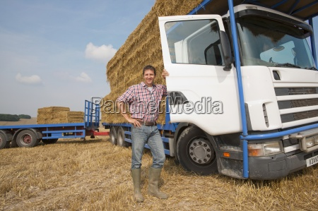 farmer standing next to lorry loaded