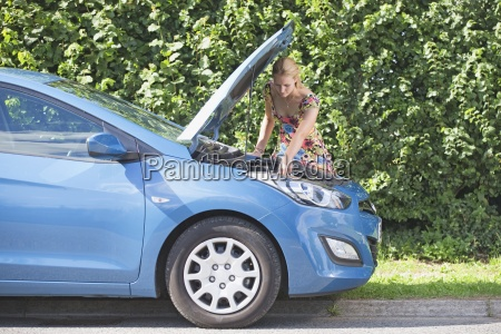woman with broken down car looking