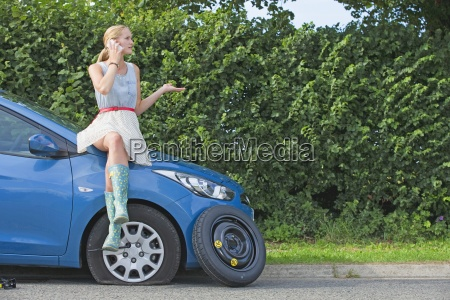 woman with flat tyre on car