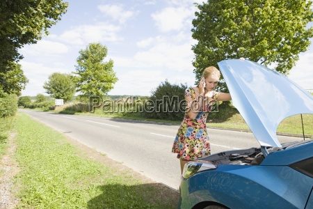 woman with broken down car phoning