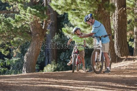 grandfather on mountain bike helping grandson
