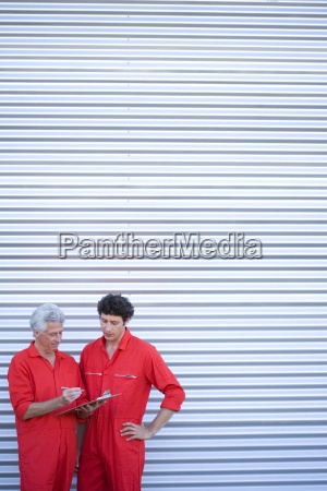 two car mechanics in red overalls