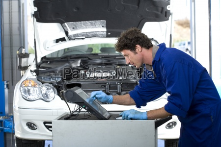 male car mechanic in blue overalls