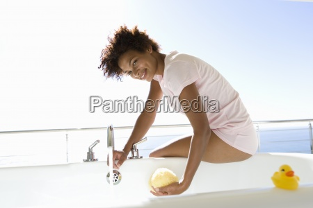 young woman sitting by bath smiling