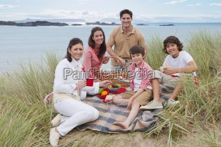 extended family having picnic in sand
