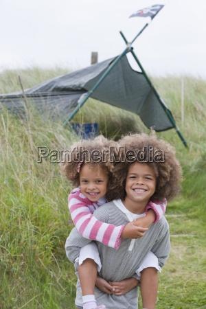 children standing in dunes next to