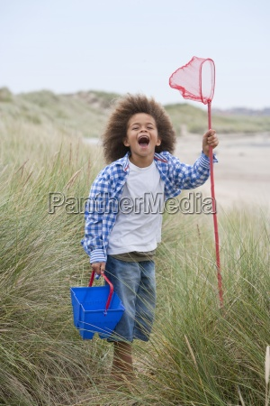 young boy standing in dunes with