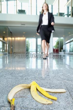 businesswoman approaching banana peel on lobby