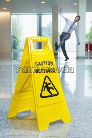 businessman slipping behind wet floor sign