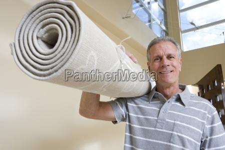 senior man carrying rolled up carpet