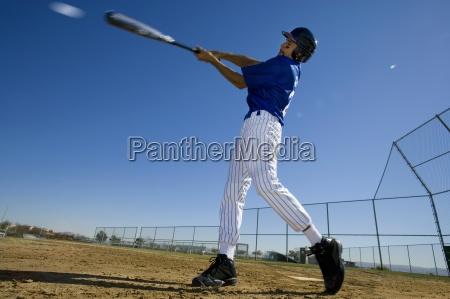 baseball batter in blue uniform hitting