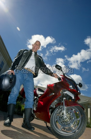 senior man standing beside motorbike on