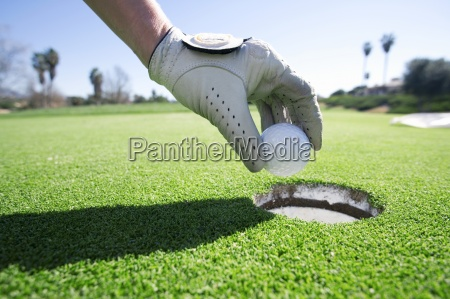 person taking golf ball out of