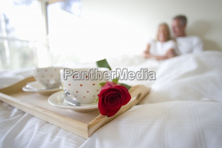 mature couple sitting upright in bed