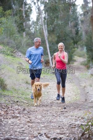 aktivt seniorpar i sportsbeklaedning jogging langs
