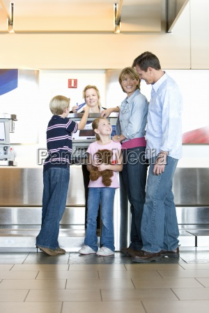 family checking in at airport check