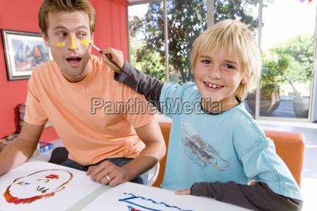 boy 6 8 putting paint on