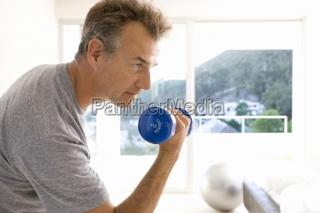 mature man lifting weight indoors side