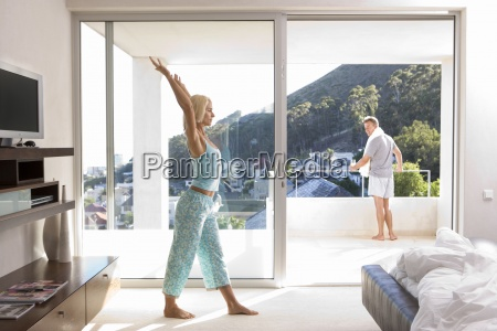 woman stretching arms in bedroom man
