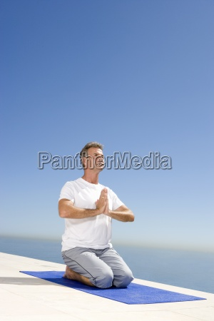 mature man meditating on exercise mat