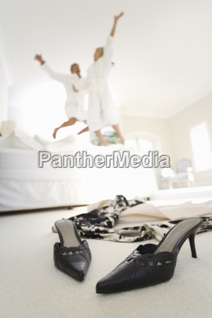 couple wearing white bath robe jumping