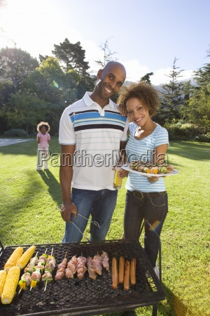 couple standing by barbeque outdoors holding