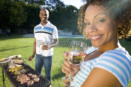 couple having barbeque outdoors woman holding