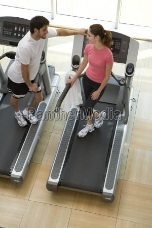 man and woman on treadmills in