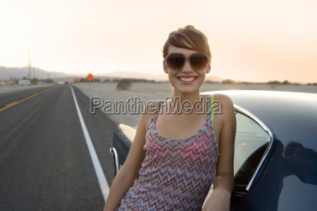 young woman in sunglasses by car