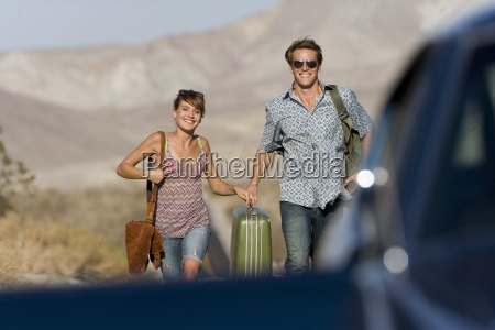 young couple hitchhiking on open road