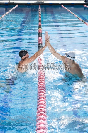 male swimmers in swimming pool giving