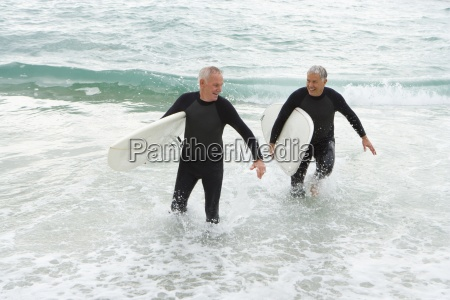 male surfers in wetsuits in shallow