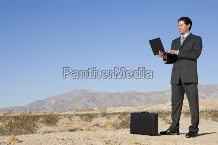 businessman by briefcase using laptop computer