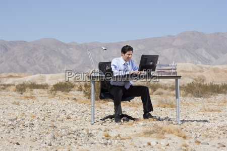 businessman at desk in desert using