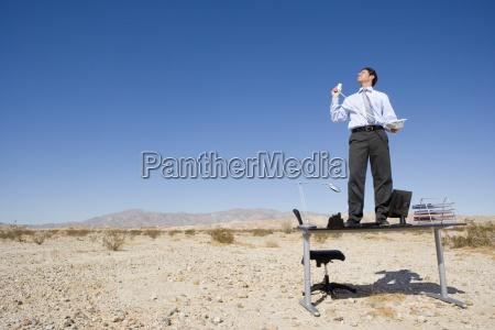 businessman standing on desk in desert