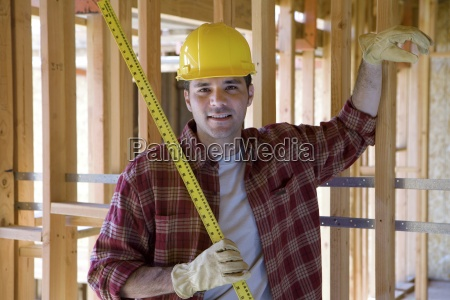 builder in hardhat with tape measure