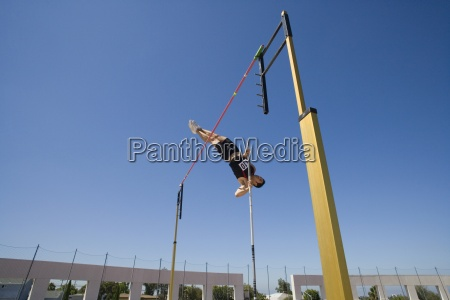 male pole vault athlete going over