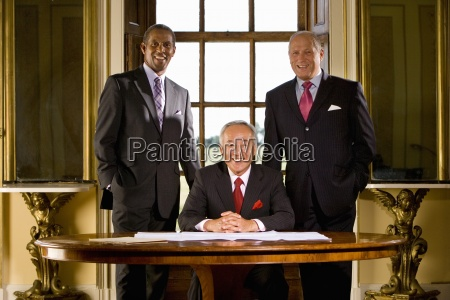 mature businessman at desk flanked by