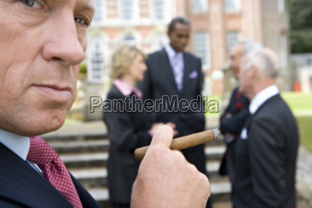 businessman with cigar by manor house