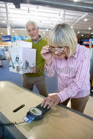 starsza kobieta placac z chipem i